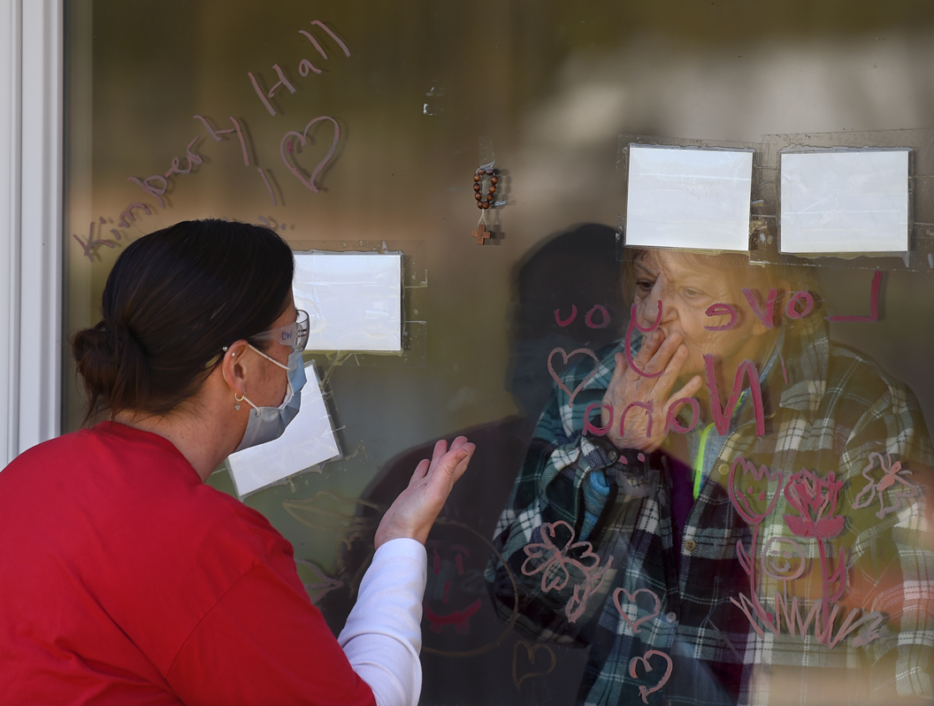 A resident and an employee of a nursing home blow kisses to one another through a window.