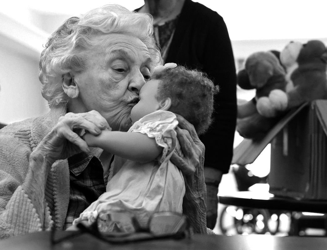 Rose Aiello gives her new doll a kiss at The Atrium at Rocky Hill Wednesday afternoon. Aiello and her fellow residents who suffer from dementia were given dolls or plush dogs Wednesday afternoon by members of the Rotary Club of Wethersfield/Rocky Hill. Aiello, a mother herself, immediately took to the doll. The goal is to give people with dementia life chores and a sense of purpose.