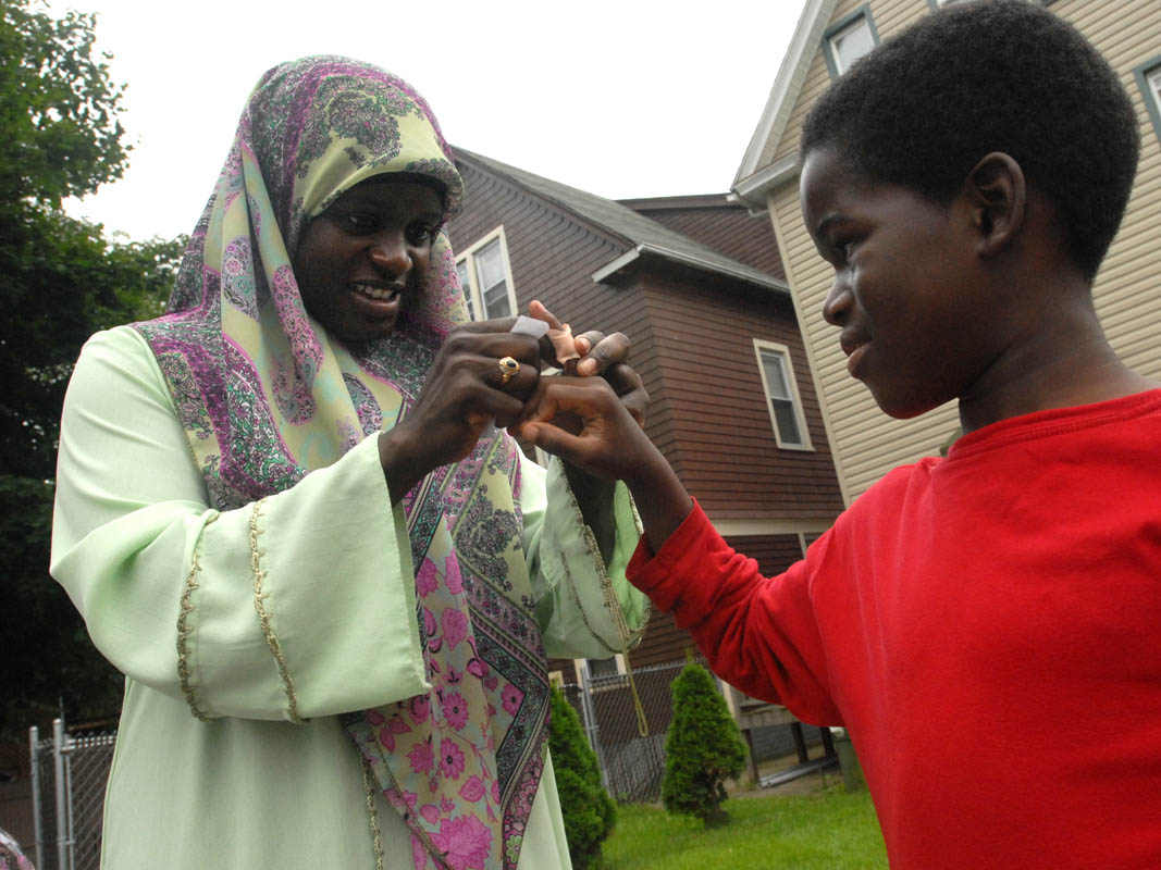 Mubarakah Imbrahim puts a bandaid on her son Ihsan's finger.