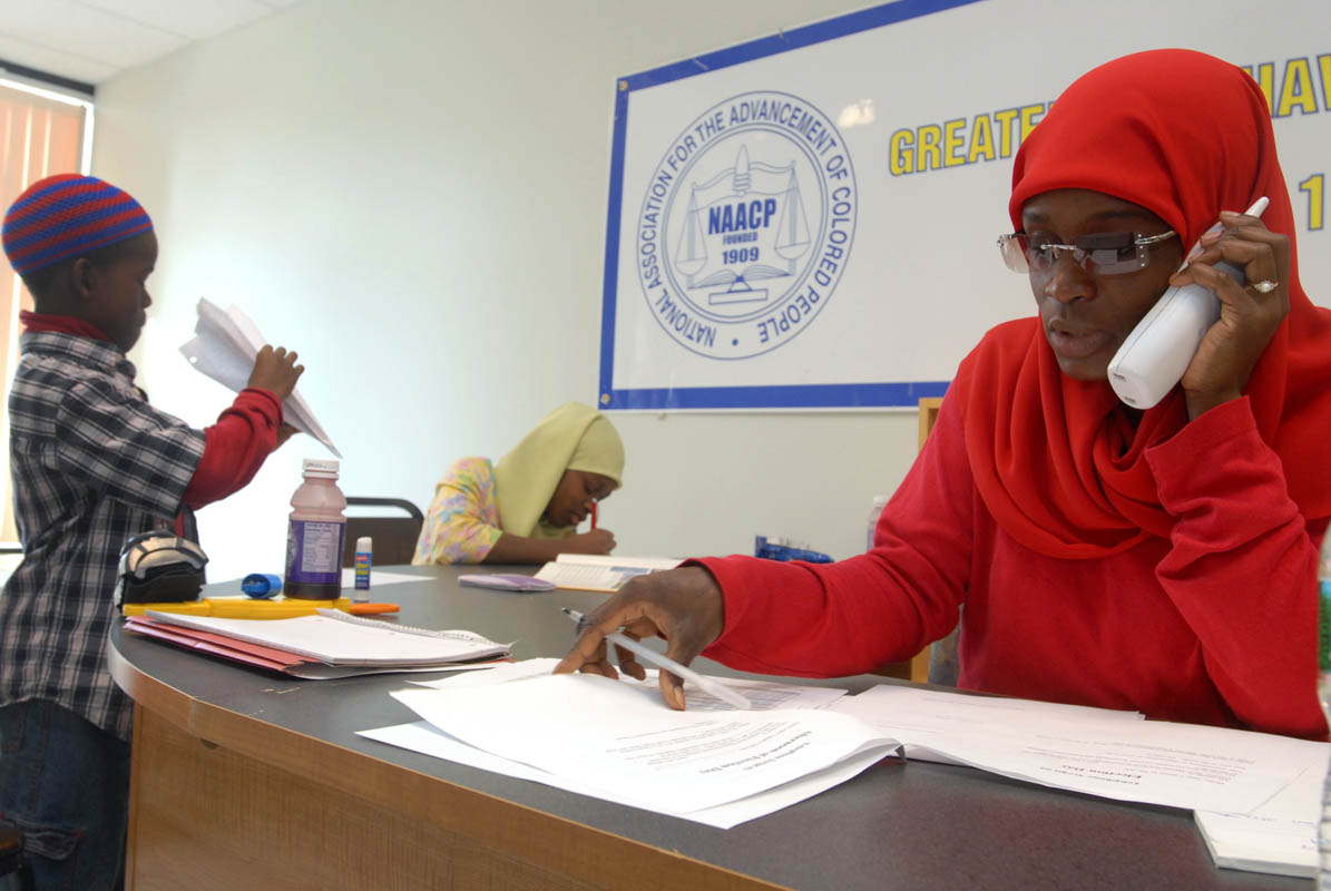 Mubarakah Ibrahim, right, volunteers at the New Haven chapter of the NAACP on election day.  As she calls to encourage people to get out and vote, her son Ihsan and daughter Salwa play and do homework.