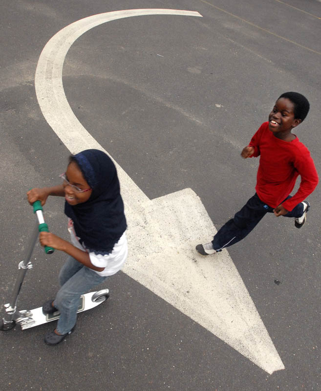 Ihsan Abdussabur chases Layla McMillan across the Masjid Al-Islam parking lot during a fundraiser for Omar Ibn Said Leadership Academy.