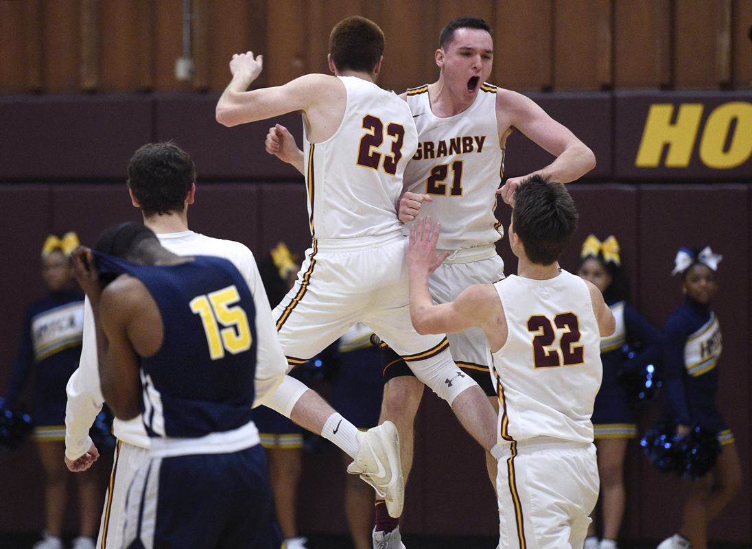 Granby Memorial players Danny Pierce, left, and James Shelansky, right, celebrate with teammate Rowan Heinze, center, after Heinze sunk the game-winning basket as the clock expired against HMTCA in an NCCC boys' basketball semifinal game at Granby Memorial High School Wednesday afternoon. At far left is HMTCA's Coron Henderson.