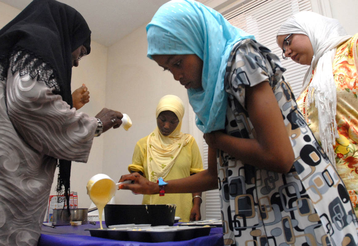 Group leader Sayidah Wilson, Saffiyah Shahid, 11, and Bilqis Hashim, 11, pour batter into cupcake molds for the evening's iftar.  Looking on at right is Khadija El-Hasimy.  The third meeting of the Muslima Girl Scouts centered around preparing food for the breaking of the Ramadan fast after dusk.