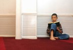 Nadeem Obaid, 11, of West Haven, reads the Qur'an after prayer at the New Haven Islamic Center.