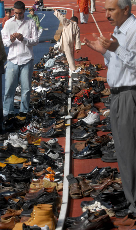 Bilal Luqman, 7, top-center, navigates a sea of shoes at Coxe Cage during Eid il-Fitr prayer.