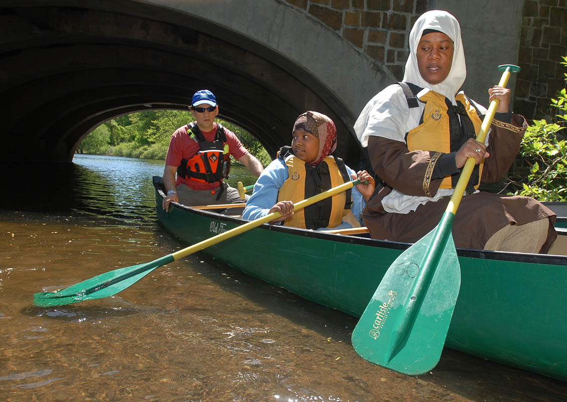 Fay Latif, right, and her daughter Adrianna Gayle, 12, listen to instructions from their canoeing guide Martin Torresquintero as they enter the Mill River.  Torresquintero is the outdoor adventure coordinator for the city of New Haven.