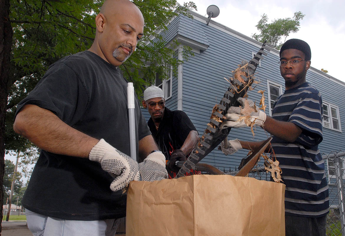 Members of a West River neighborhood block watch Humayun Malik, Russell Jones and Ibrahim Qawiyy clean up leaves and trash on Greenwood Street on Saturday morning.