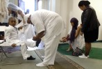Groom Abdullah Marcus Phelmetto, center, ties his son Amir's shoelaces while bride Aiesha Wilkes-Phelmetto, second from right, puts her shoe on at the conclusion of their wedding ceremony at Masjid Al-Islam.  Though she is Christian, Wilkes-Phelmetto and other non-Muslim women cover their heads while in the mosque.