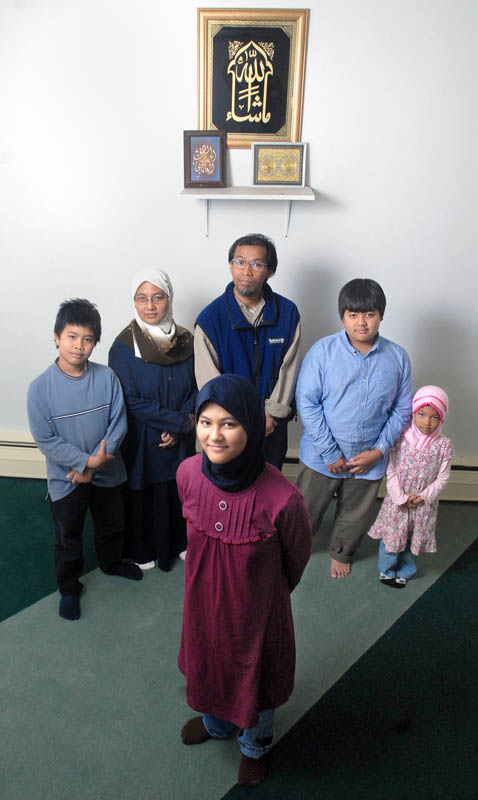 Maeda Hanafi, front, a 12 year-old girl from West Haven, will attend the University of New Haven next year.  Standing behind her are brother Idris Hanafi, 10, mother Anna Hanafi, father Imam Hanafi, brother Adam Hanafi, 11, and sister Aisya Hanafi, 5.