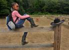 Elaisa Thomas, 9, of Hartford, prepares to watch a horseback riding barrel race in the paddock at Ebony Horsewomen Equestrian Day Camp at Keney Park.