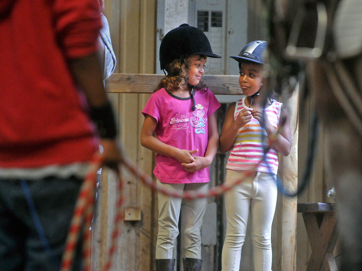 Kennedy Mattson, 6, left, and My'Azia Reynolds, 5, in the arena before riding at Ebony Horsewomen Equestrian Day Camp at Keney Park.