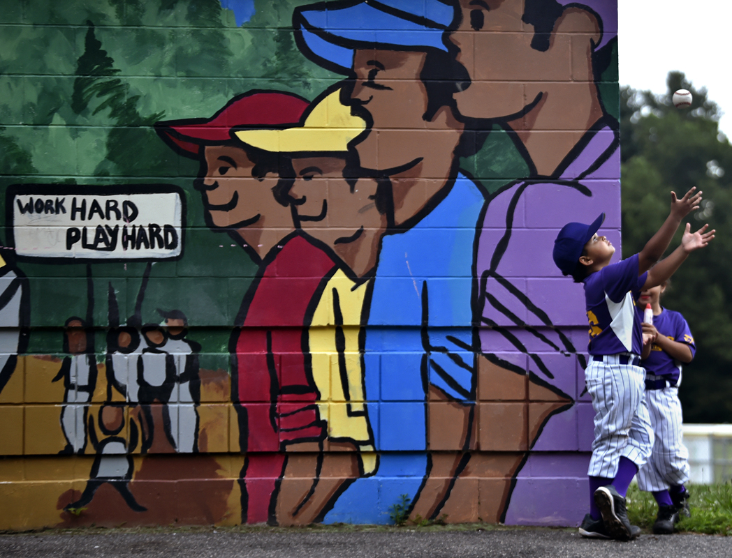 The Ques little leaguer Jeremiah Amaro catches a baseball after his game in the Hartford Northend 5-8 (year) Little League at Waverly Field Wednesday evening.