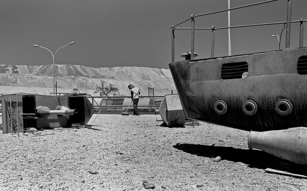 A municipal worker sweeps the ever-present dust on a playground at Chuquicamata.  Codelco, the state-owned copper company  has created