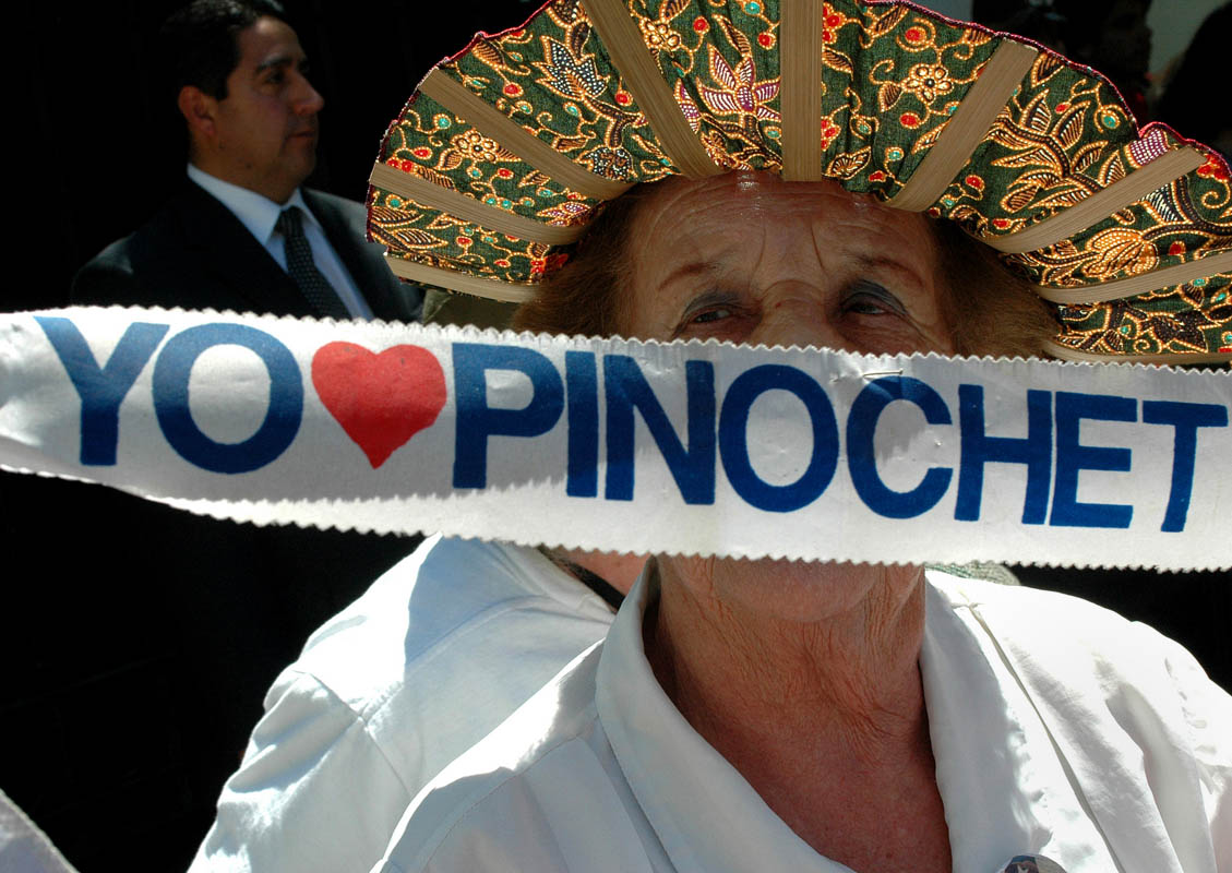 A supporter of former-dictator Augusto Pinochet supporter outside his home on his 90th birthday.