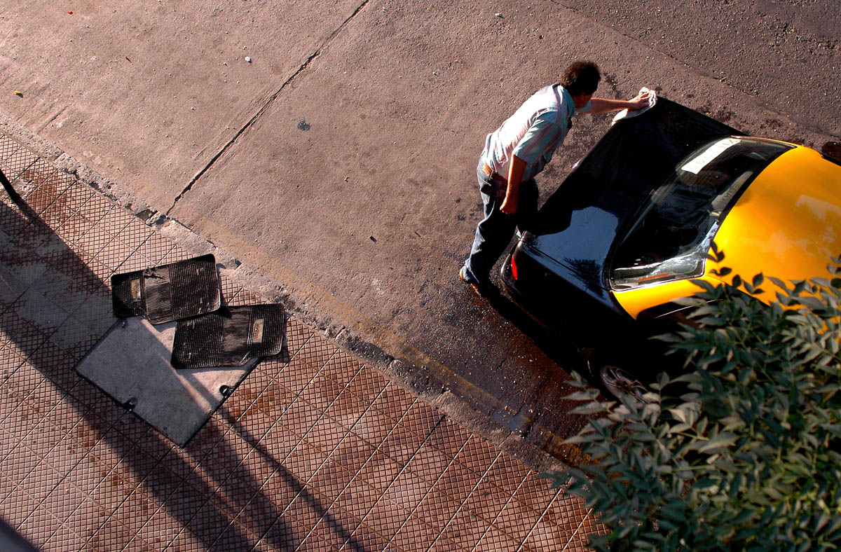 A cab driver wipes down his car in the early-morning Santiago light.