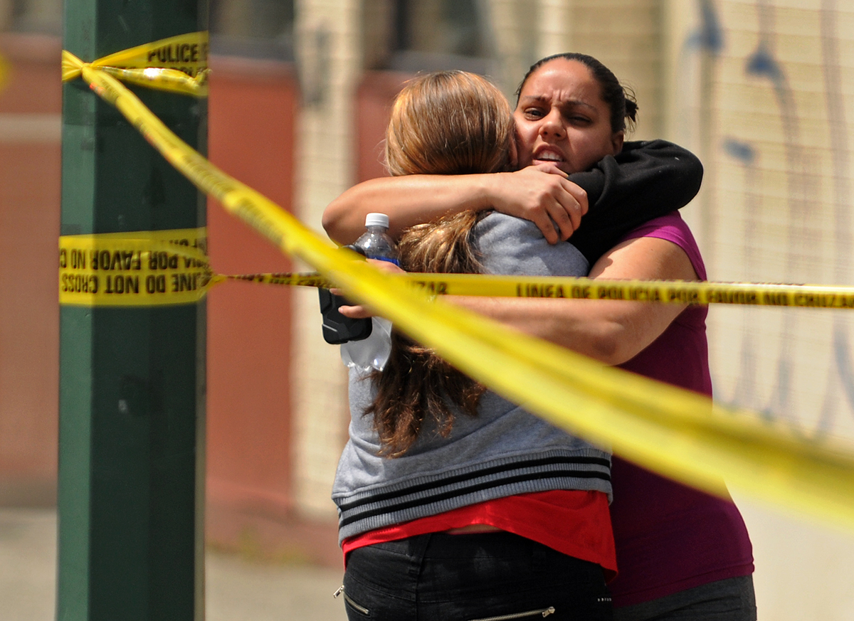 Brenda Girouard hugs her daughter Brenda Lee Alvarez, facing, an employee at the Family Dollar store where a shooting took place late Saturday morning. Shots were fired and two, including the gunman who shot himself, were rushed to the Hartford Hospital. Later, Alvarez was not hurt in the incident.