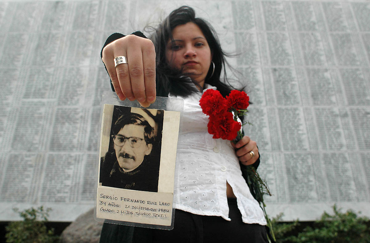 In front of a memorial for those missing, a young woman holds up a photograph of her uncle who went missing during the Pinochet dictatorship.