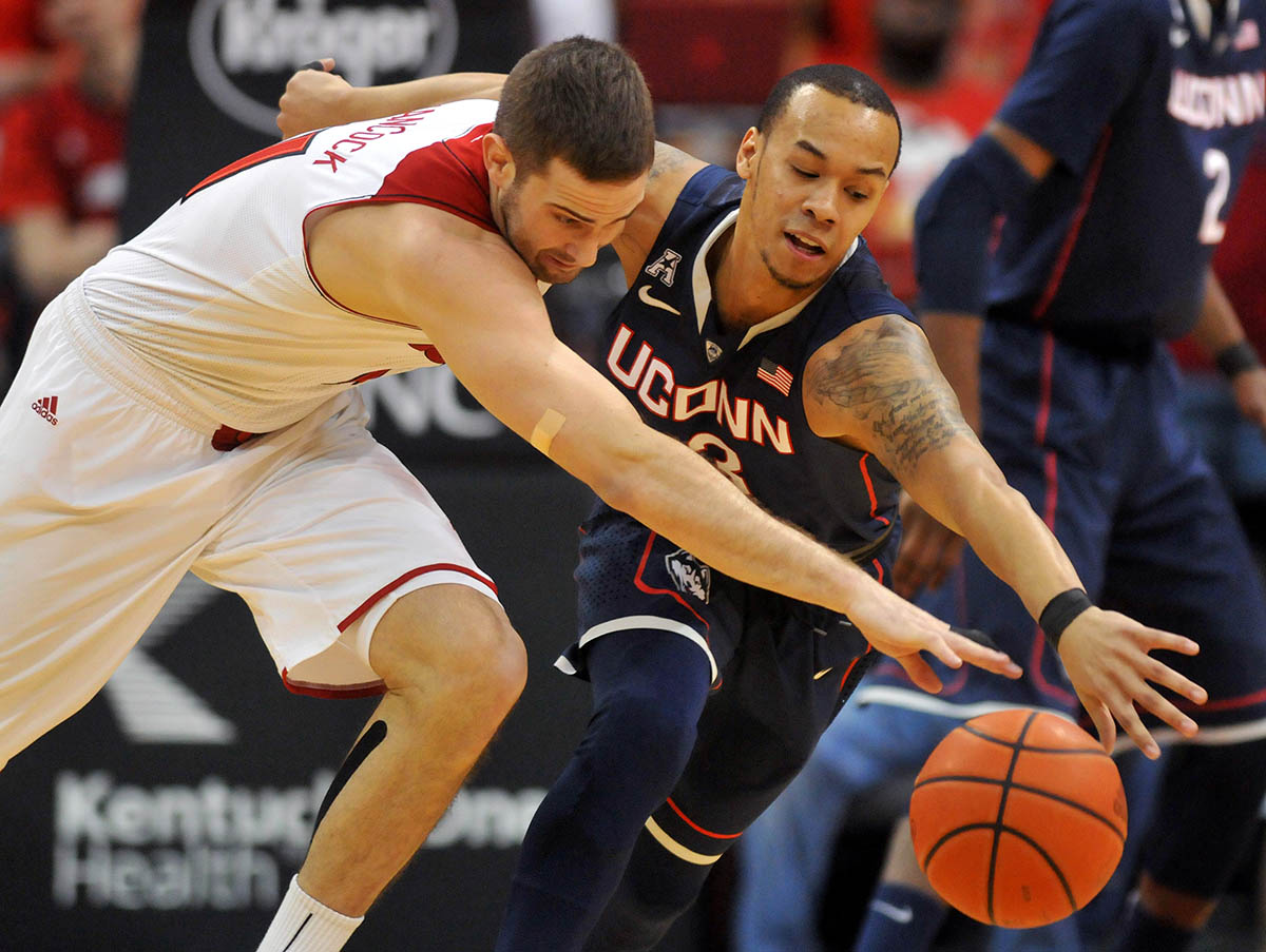 UConn's Shabazz Napier battles Louisville's Luke Hancock for a loose ball at the KFC Yum! Center.