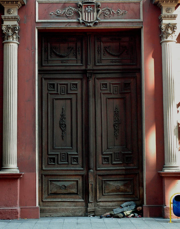 A homeless woman lay in the giant doorway of the Basilica de la Merced in downtown Santiago.