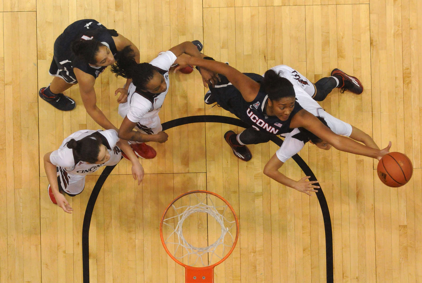 Connecticut Huskies forward Morgan Tuck (3) grabs a rebound among several Cincinnati Bearcats at Fifth Third Arena Sunday afternoon.  UConn won the game 96-31. Looking on is Connecticut Huskies forward Gabby Williams (15).