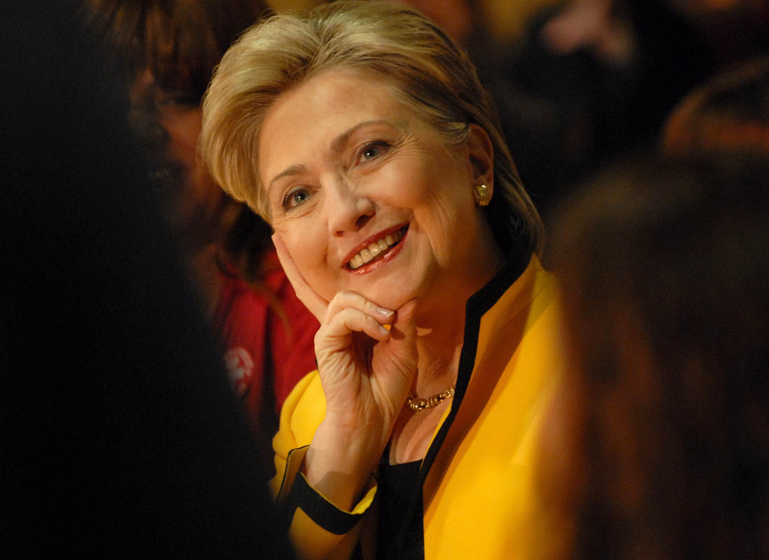 Hillary Clinton smiles at a friend who speaks up on her behalf at a round-table discussion in New Haven.