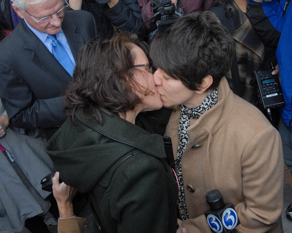 Jen Vickery and Peg Oliveira kiss during their marriage ceremony outside of New Haven City Hall while appellate court judge Herb Gruendel looks on.  Jen and Peg were the first same-sex couple to be married in Connecticut.