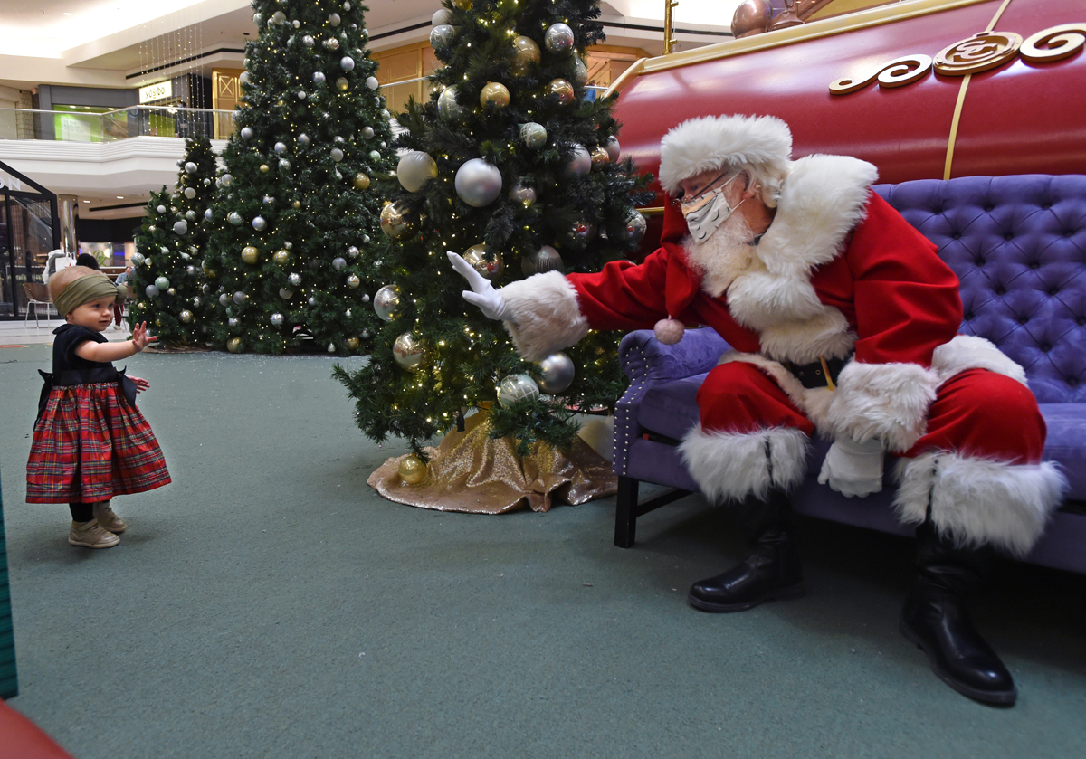 A young girl waves to Santa Claus at Westfarms Mall Tuesday. Westfarms is offering socially-distanced photos with Santa to accommodate for the pandemic.