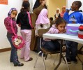 As students line up to leave the cafeteria, kindergartener Arshiya Mohamed, seated, appears displeased.