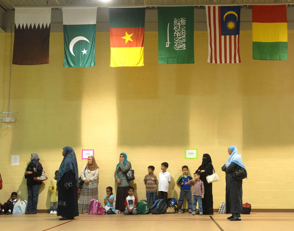 Parents, faculty and students stand in the gymnasium during orientation on the first day school.