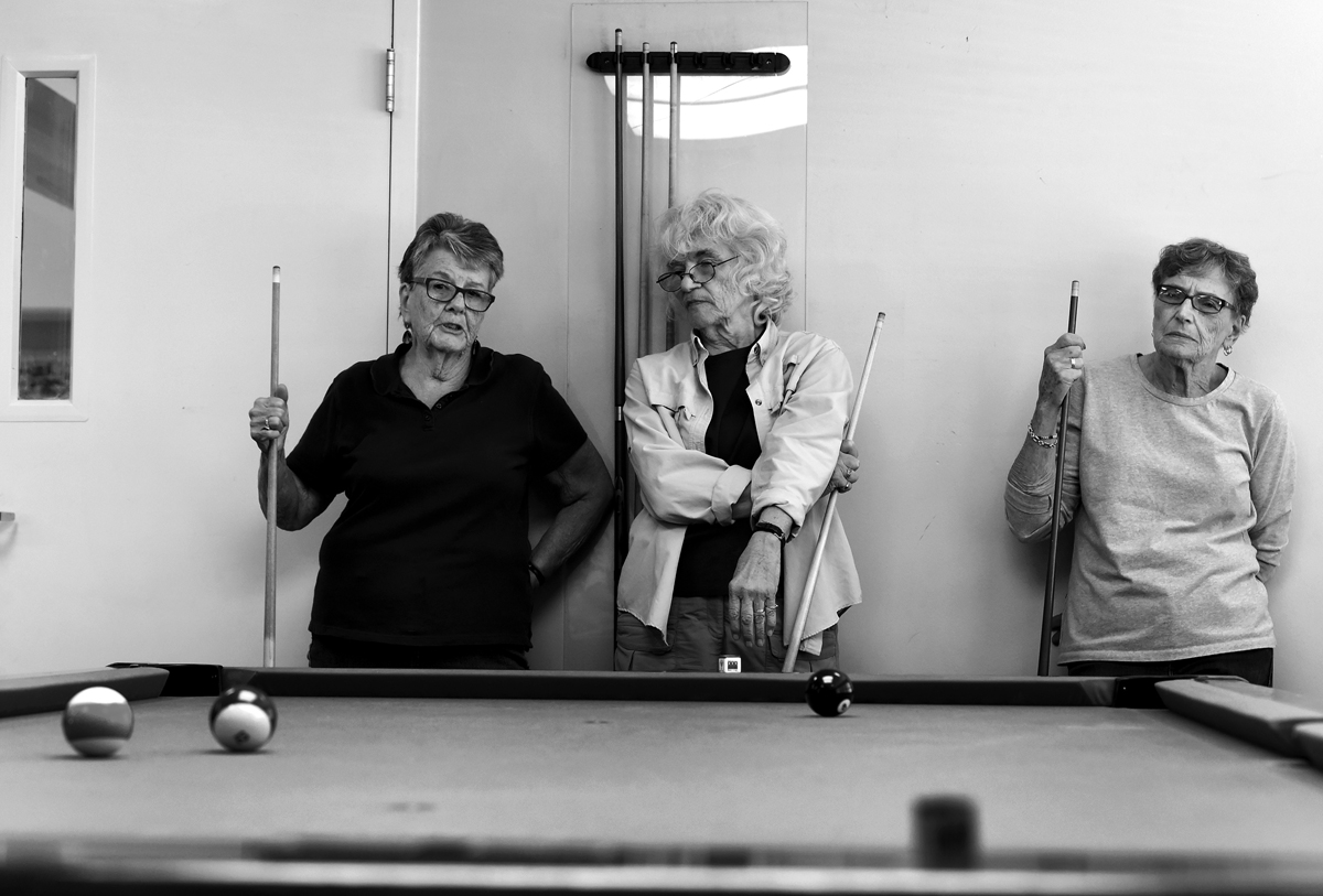 Ellen Couture, left, Patti Cancelli, center, and Jeanne Shugruelook on during a weekly coed pool tournament at the Plainville Senior Center Thursday afternoon.