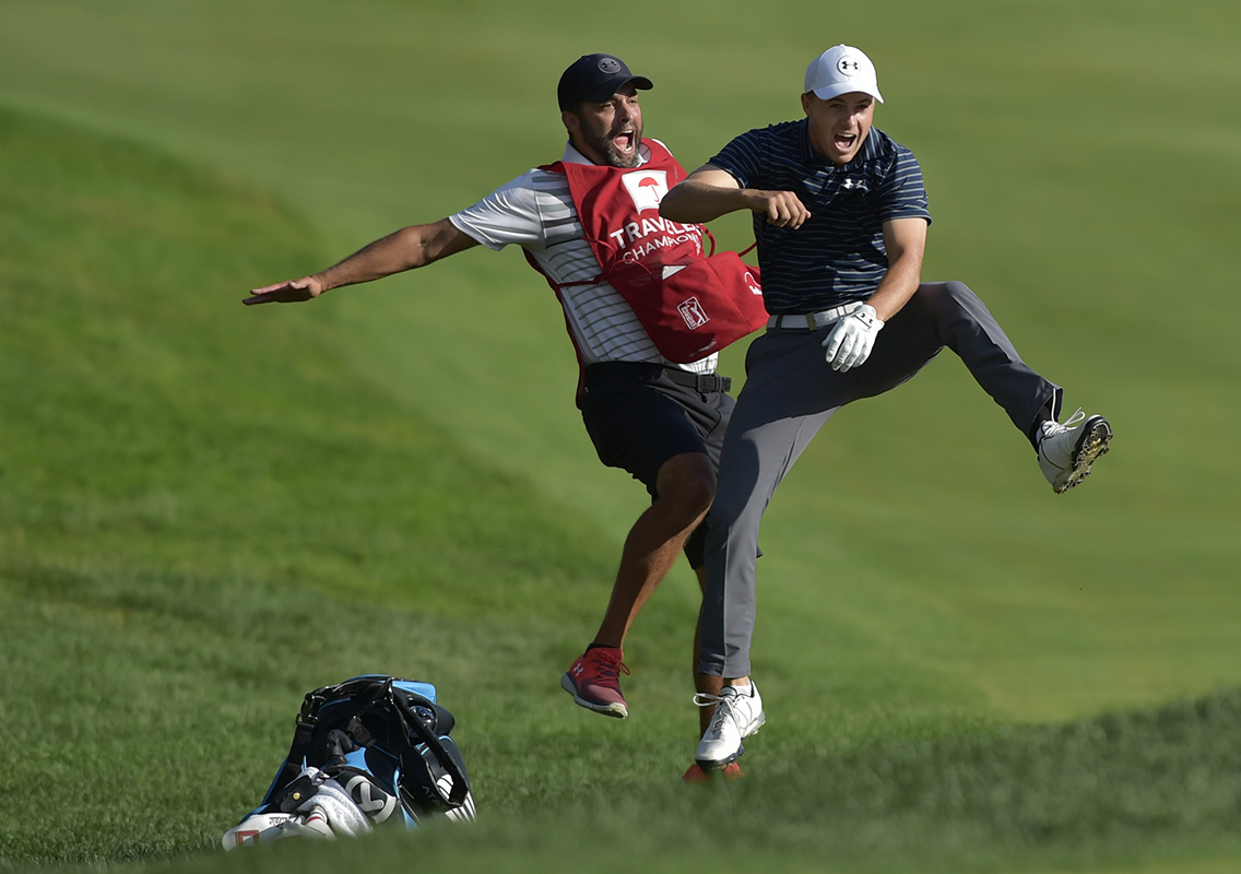 Jordan Spieth, right, celebrates with caddie Michael Greller after Spieth holed a bunker shot on a playoff hole on the 18th hole to win the Travelers Championship golf tournament.