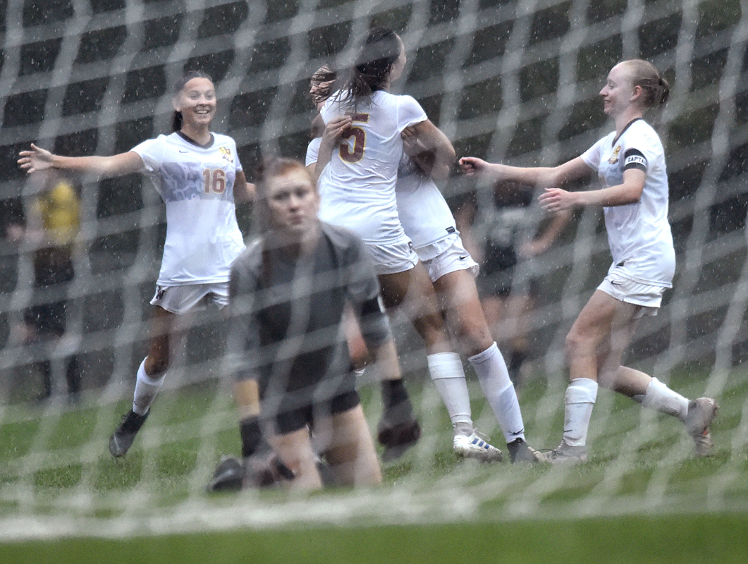 Mansfield, CT - 9/26/19 - Goalscorer Caitlin Sauer (5), center, celebrates with teammates Emma Smith, facing center, Jordan Roberts, left, and Lindsay Fishman, right, at Farrell Field in Mansfield Thursday as EO Smith goalie Rachel Hughes looks into the goal. South Windsor won the game 2-1.