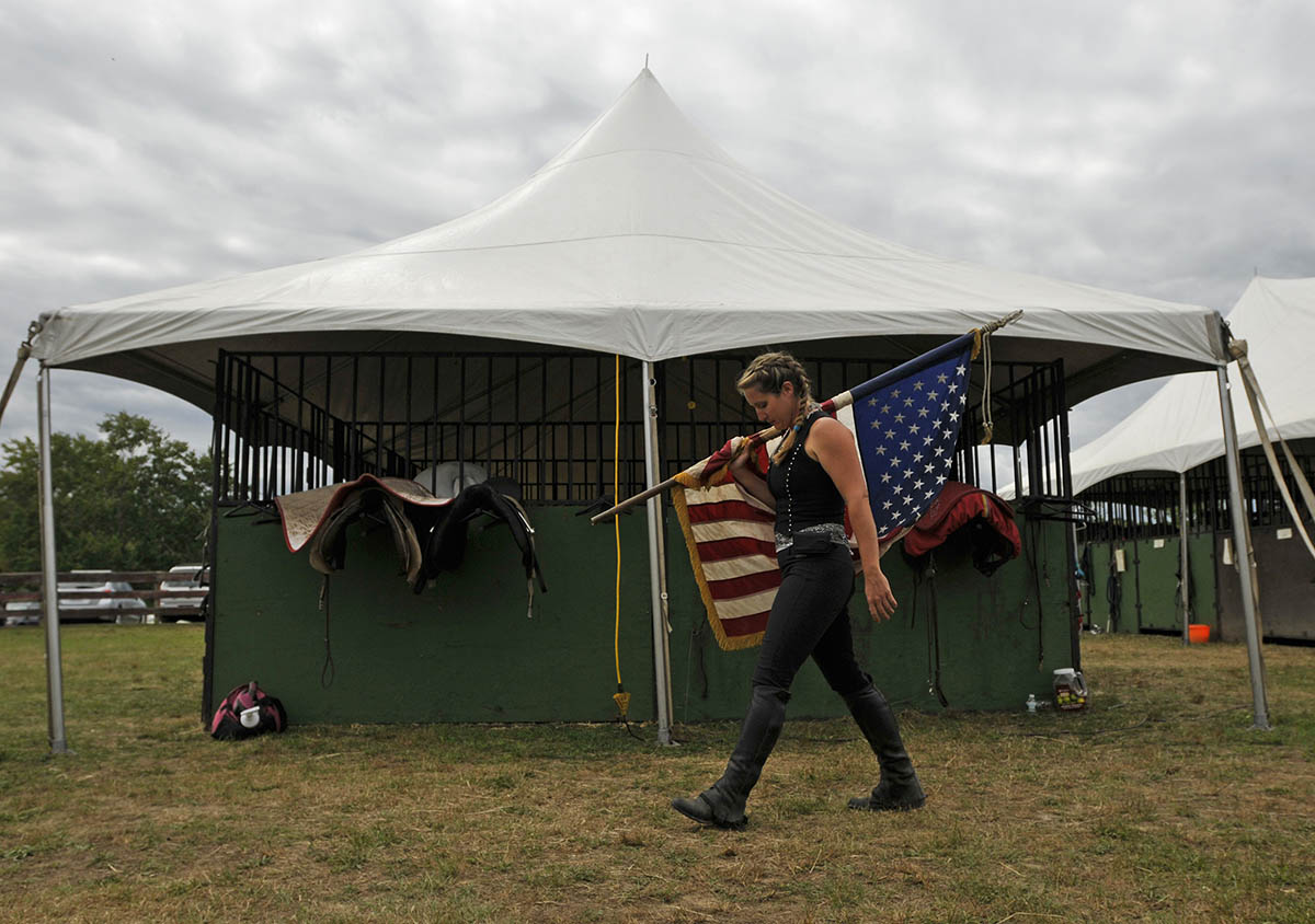 Rebecca McCullough, rider/trainer for Herrmann's Royal Lipizzaner Stallions carries Old Glory before Saturday's performance at Mitchell Farm Equine Retirement.