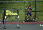 A boy pretends to play guitar with his tennis racquet at Phil Gordon Tennis Unlimited Summer Camp at Elizabeth Park.