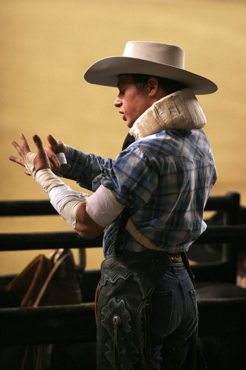 A bullriding contestant tapes up before the competition at the Pennsylvania Farm Show rodeo.