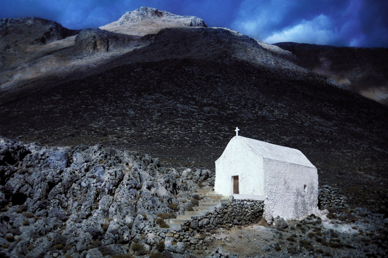 Built on the rocky slopes this Greek chapel stands along the footpath from Loutro to Glyka Nera Beach. Island of Crete. Greece.