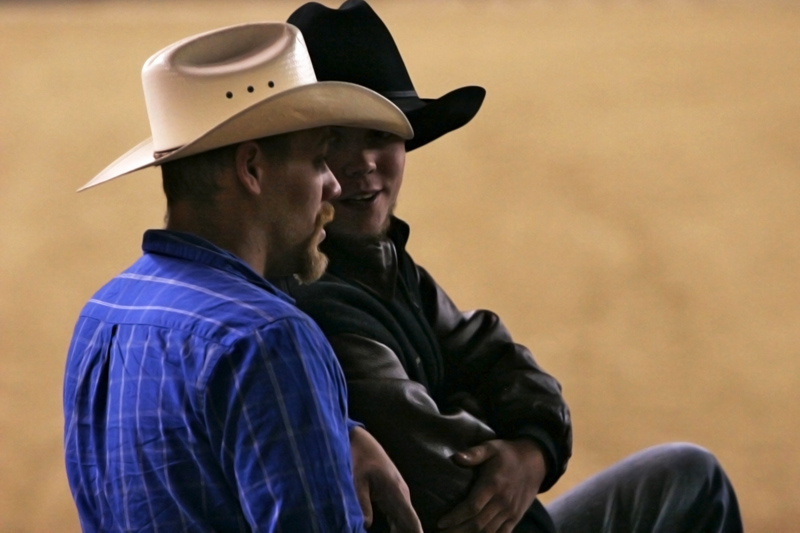 Rodeo contestants relaxing by the chutes.