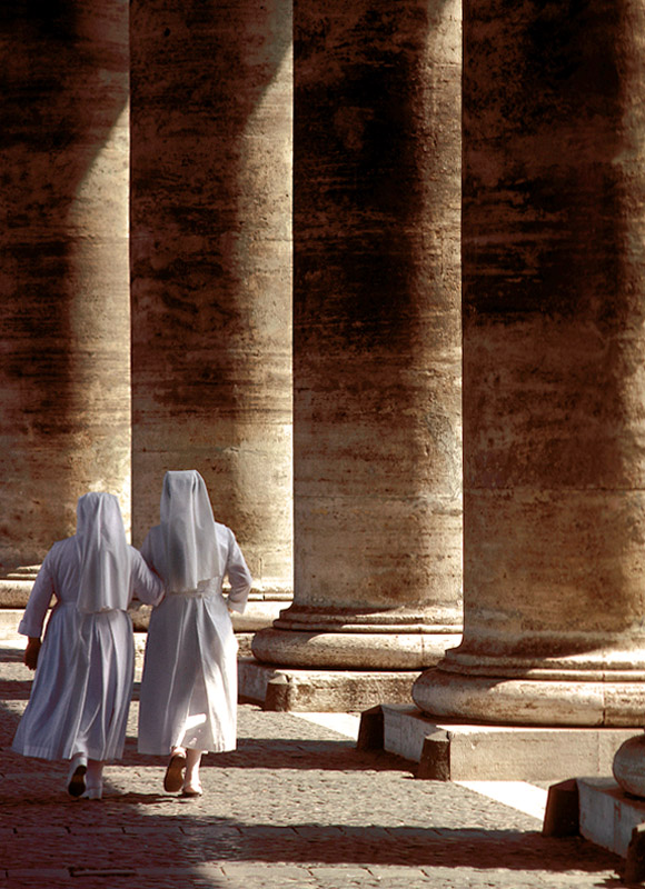 Out for a stroll, these two nuns are walking arm-in-arm under the enormous Doric columns that comprise Bernini's famous colonnades at St. Peter's Square in the Vatican City.