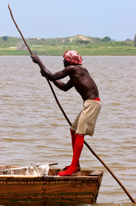Poling his boat on {quote}Lac Rose{quote} (Pink Lake), this man is part of the small salt-collecting industry located here northeast of Dakar. Salt collectors protect their skin with shea butter and wear stockings. Salt content in the lake is close to 40%.
