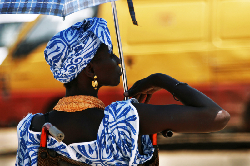 Next to a traffic stop shaded by her unbrella, this woman in her wheelchair is in position to wait for alms. Almsgiving is part of life in Senegal. Muslims believe those who are better off have a duty to act charitably toward those who are less fortunate. And, they approve the collection of alms by those individuals suffering in poorer circumstances. In effect, one cannot give alms if no one is present to receive them.