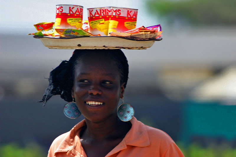 Both men and women are in the custom of carrying items atop their head, but more often women. Perhaps the daily tasks men perform are different in nature and more often require the use of carts and tools. This young woman is wearing a sports shirt. Older women tend to prefer traditional attire, setting aside shirts and pants when they are no longer flattering.