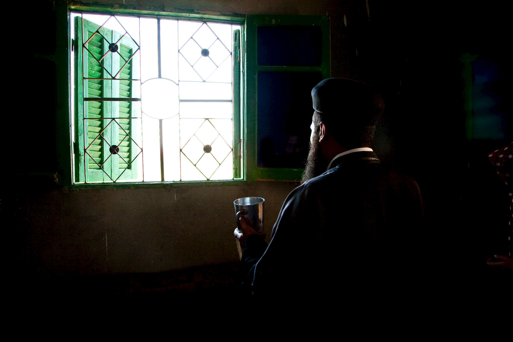 A Coptic priest sanctifies water to be used to bless a home and its family. El-Diabiyya.