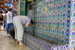 A man performs ritual ablutions before prayer at a public fountain in the Grand Bazaar.