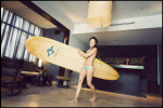 Hotel guest Betsy Bergenvin totes her surfboard through the lobby of Hotel Renew in Waikiki shot for The New York Times.