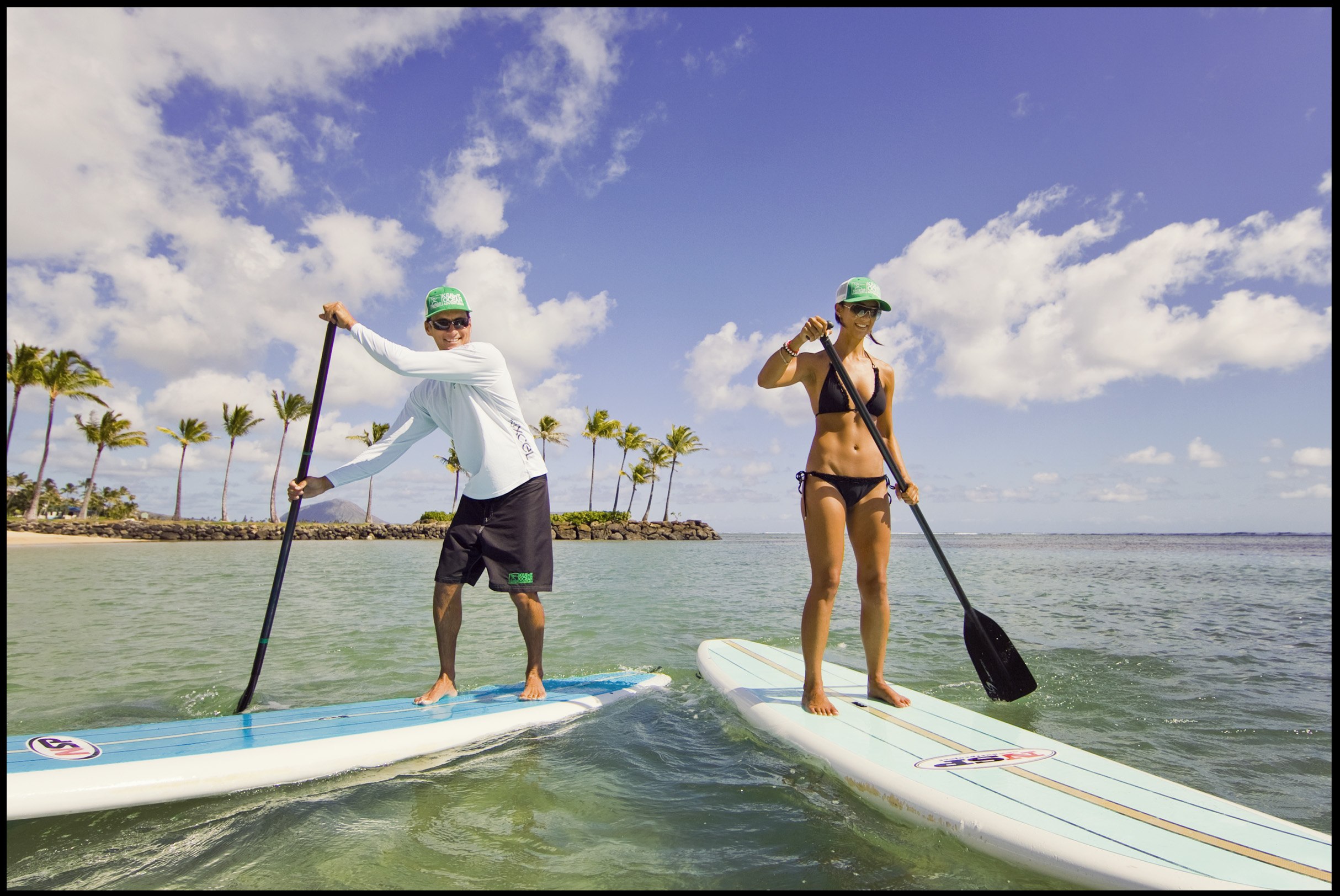 Paddleboard instructor, Makani Christensen, left, gives a lesson to Bianca Gross at the Kahala Resort in Honolulu. Photo for The New York Times.
