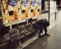 A man sleeps under a movie poster in Tokyo.