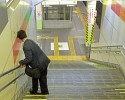 A businessman stumbles down the stairs trying to catch a late night train to get home, Chiba.