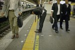 A salaryman dry heaves on the train platform after a night of heavy drinking, Chiba.