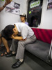 A Japanese businessman holds his head apparently after heavy drinking while aboard the Tokyo metro.