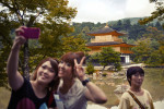 Tourists take pictures in front of the Kinkaku-ji Temple in Kyoto.  Japanese and foreign tourists braved the summer heat to see some of Kyoto's most famous sights.  The Buddhists temple is covered in pure gold leaf.